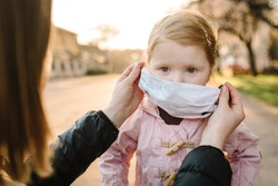 Coronavirus and Air pollution concept. Little girl and mother wearing masks walk on street. Mom corrects mask child. Pandemic virus symptoms. Family with kid outdoors. Illness protection.