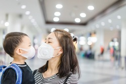 Coronavirus and Air pollution pm2.5 concept.Little chinese boy and chinese mother wearing mask for protect pm2.5 and kissing mom in Airport terminal.Wuhan coronavirus and epidemic virus symptoms.