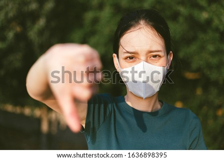 Coronavirus and Air pollution pm2.5 concept.Woman wearing mask for protect pm2.5 and show thumb doen gesture for stop corona virus outbreak.Wuhan coronavirus and epidemic virus symptoms. Stockfoto ©