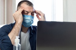 Coronavirus And Coronacrisis. Stressed Man At Laptop Massaging Temples Having Business Problems Sitting At Home. Selective Focus