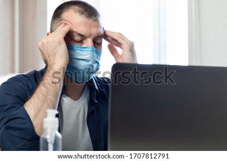 Coronavirus And Coronacrisis. Stressed Man At Laptop Massaging Temples Having Business Problems Sitting At Home. Selective Focus