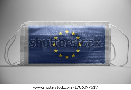 Coronavirus and restrictions in Europe Concept.Dramatic atmosphere EU  Europe Union Flag printed on surgical protective mask.Impact of pandemic virus to EU economy.
