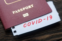 Coronavirus and travel concept, a note COVID-19 in tourist passport. Medical test at border control due to COVID. Business and tourism hit by corona virus, restrictions during coronavirus pandemic.