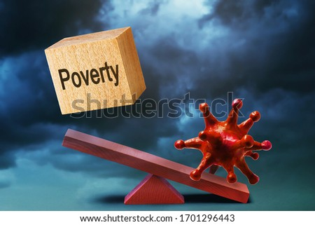 Coronavirus and wooden cube with text on a swing against a stormy sky. The concept of rising poverty due to the covid-19 pandemic Foto d'archivio ©
