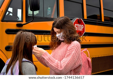 Coronavirus back to school reopening: Girls, children, students, with face masks by school bus. For Education, Health, Safety, and Environmental concepts regarding coronavirus, schools, and facemasks.
