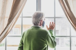 Coronavirus. Back view of a senior white haired man with green sweater in solitude at home behind the window, wearing a protective face mask due to coronavirus infection - elderly people in quarantine