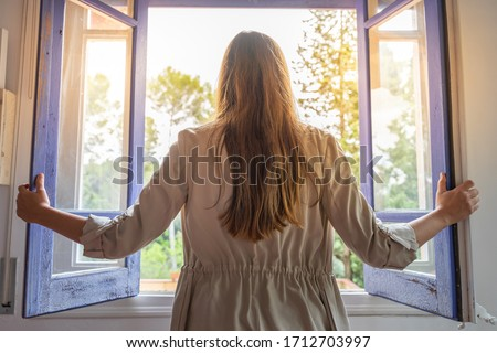 Coronavirus. Beautiful young woman isolated at home opening the window. Looking through the window. recovery from the infection. Quarantine. Isolated to prevent infection. Getting out from home. Foto stock ©
