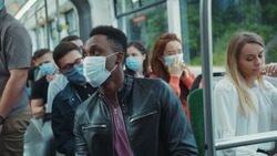 Coronavirus. Blonde woman sneezes allergy inside public tram. Scared people passengers immediately wearing face masks for virus prevention. Pandemic. Fun scene.