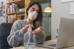 Coronavirus. Business woman working from home wearing protective mask. Business woman in quarantine for coronavirus wearing protective mask. Working from home.  Cleaning her hands with sanitizer gel.