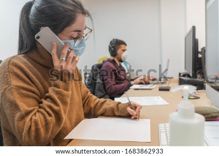 Coronavirus. Business workers working from home wearing protective mask. Small company in quarantine for coronavirus working from home with sanitizer gel. Small company concept.