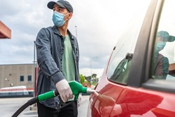 Coronavirus. Car refueling on petrol station. Man with face mask pumping gasoline oil during quarantine. Automotive industry or transportation and ownership concept. Delivery service concept. Isolated