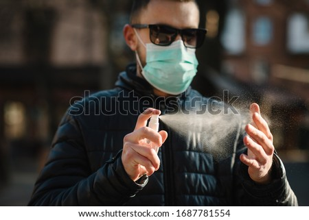 Coronavirus. Cleaning hands with sanitizer spray in city. Man wearing in medical protective mask on street. Sanitizer to prevent Coronavirus, Covid-19, flu. Spray bottle. Virus and illness protection.