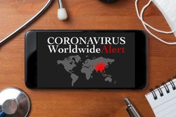 Coronavirus concept: a smartphone sorrounded by a stethoscope, a medical mask and other objects with a world map and an alert text on display