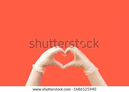 coronavirus concept hands wearing latex gloves creating a heart shape on a red background