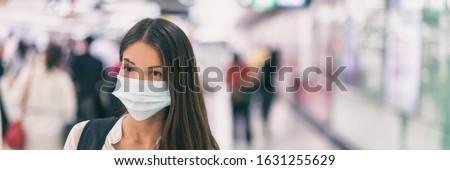 Coronavirus corona virus Asian woman wearing flu mask walking on work commute in public space transport train station or airport panoramic banner.