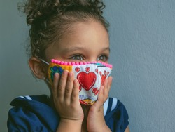 Coronavirus Covid-19 2020. A little girl wearing face mask with hearts print is clutching her face with surprise. Stay home.Social distancing.New normal behavior.