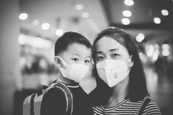 Coronavirus covid-19 concept.Little chinese boy with mother wearing N95 mask for protect from coronavirus for back to school.School kid go to school with mom.New normal lifestyle post coronavirus.