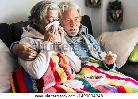 Coronavirus CoVid-19 Couple old aged senior people at home with seasonal winter cold illness disease  sit down on the sof together forever - health problems for retired man and woman with white hair