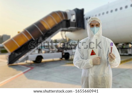Coronavirus covid 19 disease expert with full virus protective suit holds tablet with covid 19 sign and infected coronavirus blood sample with blurred airplane and stair truck