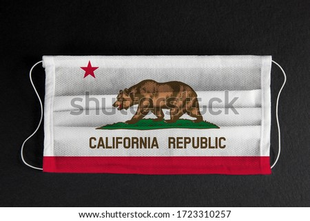 Coronavirus Covid-19 in California U.S. state. Flag of the State of California printed on medical mask on black background. Coronavirus update in California. State healthcare concept.