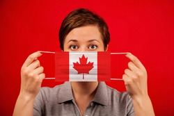 Coronavirus COVID-19 in Canada. Woman in medical protective mask with the image of the flag of Canada.