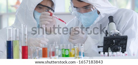 coronavirus covid-19 infected blood sample in sample tube on hand of scientist in biohazard protection clothing doing analysis to corona virus covid 19 sample in laboratory