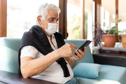 Coronavirus CoVid-19 man old aged senior at home sit down on the sofa in medical mask. watch his phone during the pandemic