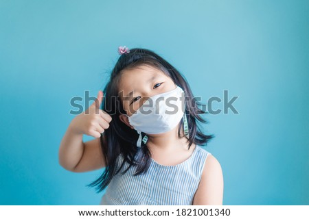 Coronavirus Covid-19.Online education at home.Asian kid girl wearing face mask show thumbs up for good and happy.Home school kid with Covid19. Online learning.Stay home.Social distancing.New normal.