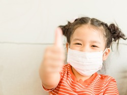 Coronavirus Covid-19.Online education.Little asian kid girl wearing face mask show thumbs up for Thank you doctor, Happy at home. Covid-19 coronavirus.Stay home.Social distancing.New normal behavior.