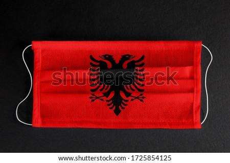 Coronavirus covid pandemic in Albania. Flag of  Albania printed on medical mask on black background. National healthcare system concept. Covid-19 outbreak, quarantine in Tirana, Albania