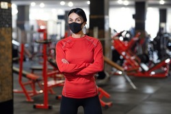 Coronavirus covid-19 prevention, fitness girl with a medical mask posing in gym. Fighting viruses.