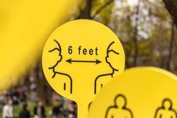 Coronavirus Covid-19 social distancing sign warning people to stay six feet apart