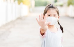 Coronavirus Covid-19.Stay at home Stay safe concept.Little chinese girl wearing mask for protect.show stop hands gesture for stop corona virus outbreak.Coronavirus pandemic virus symptoms.Home school.