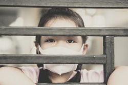 Coronavirus Covid-19.Stay at home Stay safe concept.Little chinese girl wearing mask for protect.Social distancing isolation for stop coronavirus.Coronavirus pandemic virus symptoms.Home school kid.