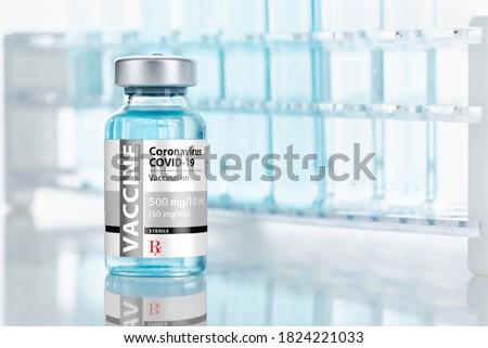 Coronavirus COVID-19 Vaccine Vial Near Test Tubes On Reflective Surface.