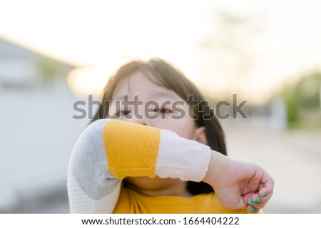 Coronavirus Covid-19 virus and Air pollution pm2.5 concept.Spreader Asian child girl sneezing on hinge joints arm outdoor for protect from virus stop corona virus covid19 outbreak.Sick child kid.