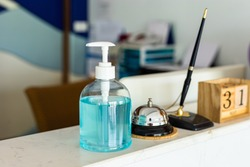 Coronavirus ( Covid-19 virus ) hand sanitizer gel or alcohol ge to wash hands at modern luxury hotel reception counter desk with bell,Pen and woodcalendar . product for airport, hospital