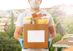 Coronavirus Donation box. Delivery food. Volunteer. Food help. A man in a mask and medical gloves holds a box of food on the street. Coronavirus volunteer. Quarantine