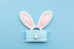 Coronavirus Easter bunny face made from rabbit ears and a protective face mask