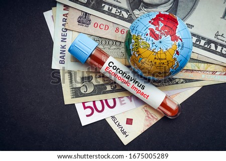 CORONAVIRUS ECONOMIC IMPACT text with currency banknotes, world globe and blood test vacuum tube on black background. Covid-19 or Coronavirus Concept