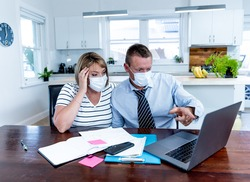 Coronavirus economic recession. Stressed couple with masks in self-isolation over home finances and small business debts during quarantine shutdown. impact of COVID-19 pandemic Global Economy Crisis.