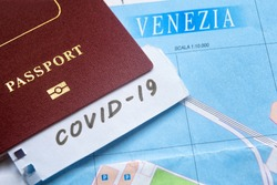 Coronavirus epidemic and travel restrictions in Italy concept. The note COVID-19 and passport on Venice map. Novel corona virus outbreak. Border control of tourists infected with coronavirus.