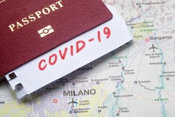 Coronavirus epidemic and travel restrictions in Italy concept. The note COVID-19 and passport on map with Milan. Novel corona virus outbreak. Border control of tourists infected with coronavirus.
