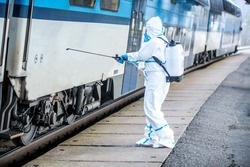 Coronavirus epidemic outbreak. Staff in clean suit disinfecting a train.