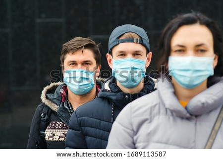 Coronavirus epidemic. People wearing face mask outdoors. Group of young volunteers. Coronavirus quarantine. Global pandemic. Worldwide coronavirus outbreak.