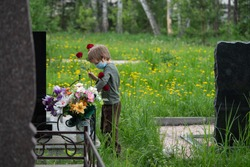 Coronavirus epidemic. Sad and Depressed boy in medical mask in Front of the Headstone, Holding a Flowers. Death, cemetery, loss of loved ones due to coronavirus concept. Tragic results of coronavirus