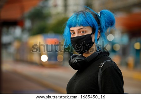 coronavirus fashionable medical face mask worn by young female student with blue anime style hair, standing at tram stop on a urban city street on dusk, stop covid 19 pandemic or air pollution concept