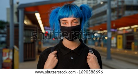 coronavirus fashionable medical face mask worn by young female student with blue anime style hair at tram stop on city street on dusk, stop covid 19 pandemic or air pollution concept, panorama banner