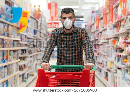 Coronavirus. Food running running out of due to Coronavirus. Empty shelves in the supermarket. Buying panic. Man wearing face mask shopping in supermarket. Protection and prevent measures.