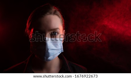 Coronavirus, girl in a mask on a black background. The title is about an outbreak of a coronavirus virus in the United States, Europe, Italy and Spain. epidemic. Photo for media headlines, news